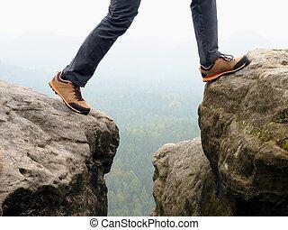 Detail of hiker legs in black orange hiking boots on mountain summit. Feet in trekking shoes