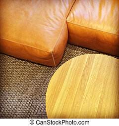 Leather sofa and round coffee table. Living room detail.