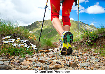 Detail of legs near the flowers of a girl who practices Nordic walking in the mountains