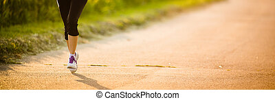Detail of legs of a female runner on road - jog workout/well...