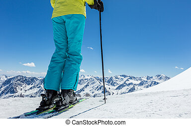 Detail of legs of young woman skier in beautiful Alpine landscape