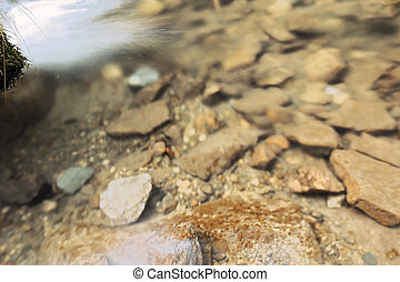 detail of mountain river bed, water flowing over rocks