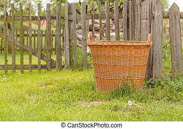 Detail of old wooden basket in front of fence