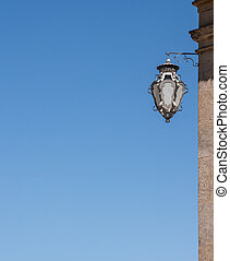 Detail of ornate lamp on side of building with blue sky