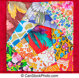 detail of patchwork quilt framed in red cloth