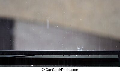 detail of raindrops falling on balcony balustrade and...