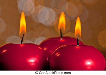 detail of red christmas candles on golden bokeh background