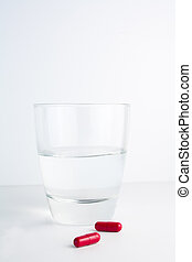 red pills next to a water glass - detail of red pills next...