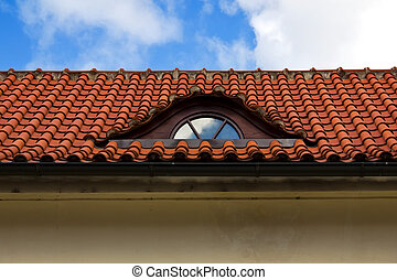 Detail of red tiled roof with garret window in Prague