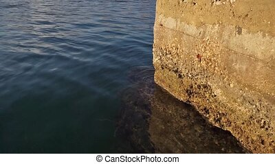 seawater waves bumping against a stone dock in a harbor -...