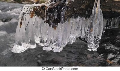 Detail of shinning icicles hanging above cold water of...