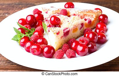 Detail of single portion of fruit pie with berries around