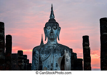Detail of sitting Buddha at sunset in Sukhothai, Thailand