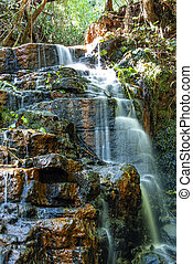 Detail of small waterfall running over rocks with moss in tropical forest in southern Brazil