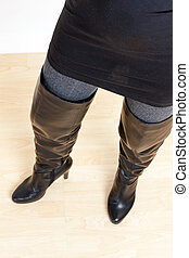 detail of standing woman wearing fashionable black boots