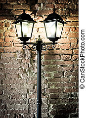 Detail of street lamp with brick wall background