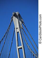 Detail of suspension bridge in front of blue sky