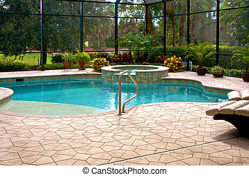 Large swimming pool surrounded by plants and screened in lanai.