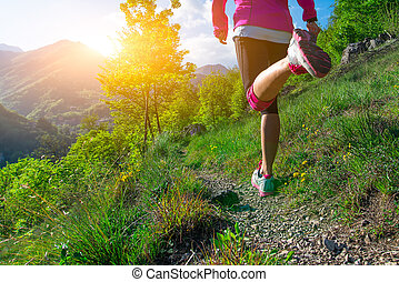 Detail of the legs of a girl running on a mountain trail