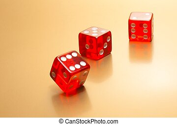 three red dice on golden background