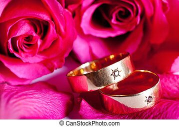 two wedding rings with red rose