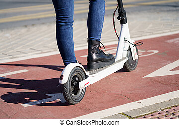 Detail of unrecognizable person using electric scooter. Lifestyle concept.