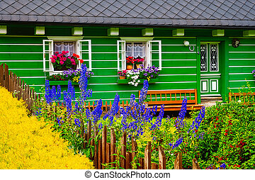 Detail of vibrant colorful cottage wall and windows with blooming flowers