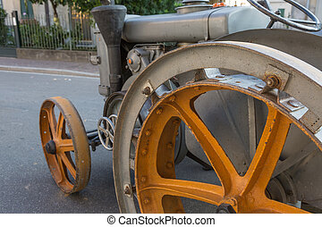 Detail of Vintage Agricultural Tractor with Yellow Metallic Wheel