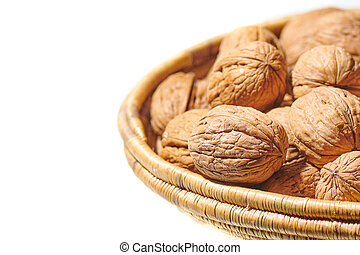 Detail of walnuts in a basket on a white background