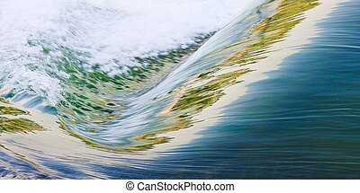 Water flowing down a waterfall with the illuminated reflected in the waves