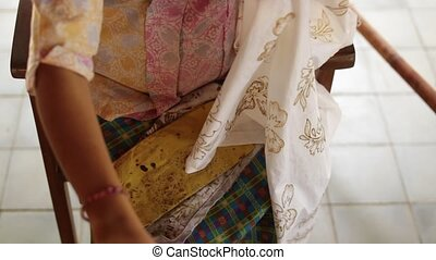 Detail of waxing the drawing to textile for making batik. Bali island.