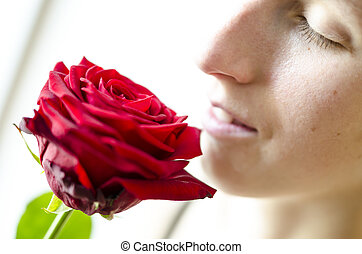 Detail of young woman smelling a beautiful red rose.