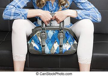 detail of woman with a handbag sitting on sofa