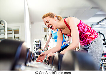 Detail of women in gym laughing, row of weights