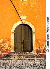 Detail of wooden door in bright orange textured wall