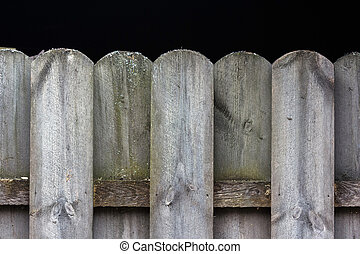 Detail of wooden fence tops pattern with black background and sp