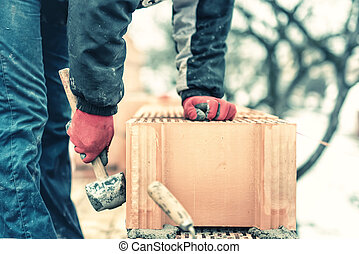 Detail of worker, bricklayer construction engineer fixing bricks and building walls at new house on a cold winter day