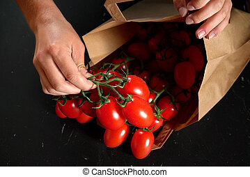 Detail on hands getting small red cherry tomatoes with green...