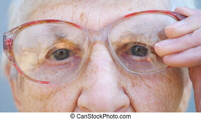 Detail portrait of granny in eyeglasses with pensive sight. Close up wrinkled face of female pensioner looking into camera and adjusting glasses. Sorrow facial expression of grandma. Slow motion.