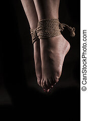 detail suspended bound feet submissive young girl on a black background / BDSM theme