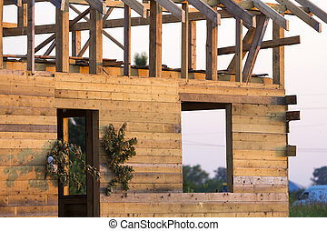 Detail view, corner of new wooden ecological traditional cottage of natural lumber materials with steep roof frame under construction in green neighborhood. Professional building concept.