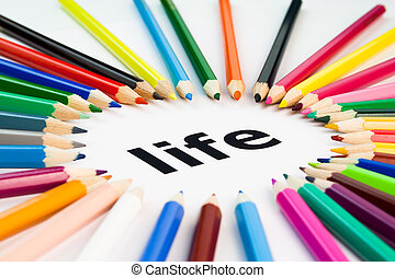 many colored pencils arranged in circle on the word life -...