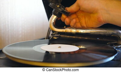 Detail view on needle sliding on black vinyl record spinning on retro turntable. Male hand taking stylus from vintage plate and turning off old gramophone. Retro concept. Slow motion Close up.