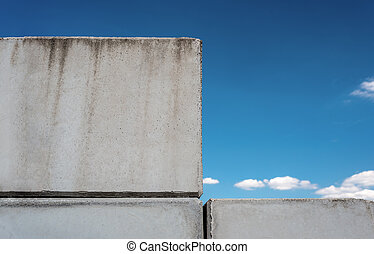 Detailed background of concrete wall photo texture on blue beautiful sky background with white clouds.
