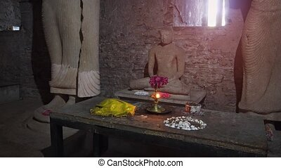 Fresh flowers offered on an altar before a stone sculpture of the Buddha, inside an ancient temple in Pollonaruwa. Video 1080p