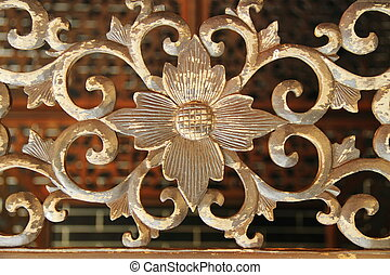 detailed carving of flower on weathered wood