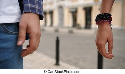 Detailed view of a young couple holding hands. They walking in the city street