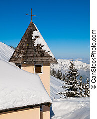 Detailed view of rural mountain church tower with cross on the top in snowy winter alpine landscape