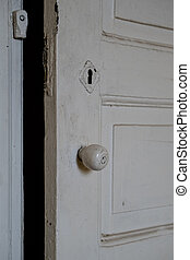 Details of a white painted wooden door of an empty abandoned...