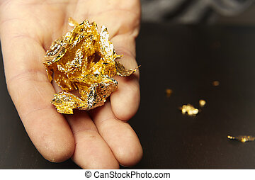 Details of metal gold leafe creased in gilder's hand - ...